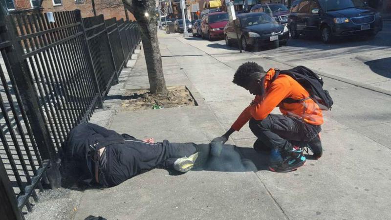 Jovem reza junto a sem-abrigo