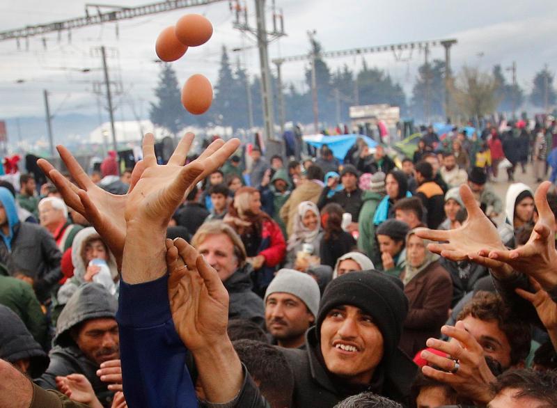 Refugiados recebem comida na fronteira da Grécia com a Macedónia