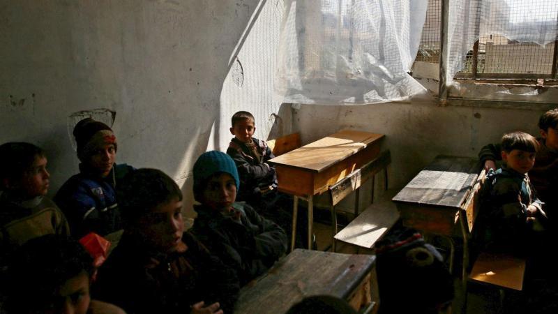 Crianças sírias limpam a escola