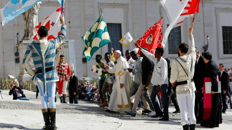 Refugiados sentam-se ao lado do Papa