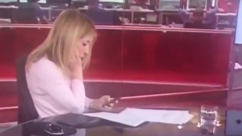 Jornalista da BBC distraída com o telemóvel em direto