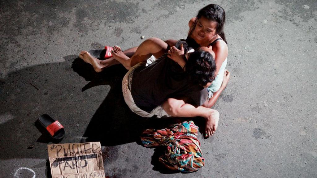 Mulher segura corpo do marido abatido devido às drogas