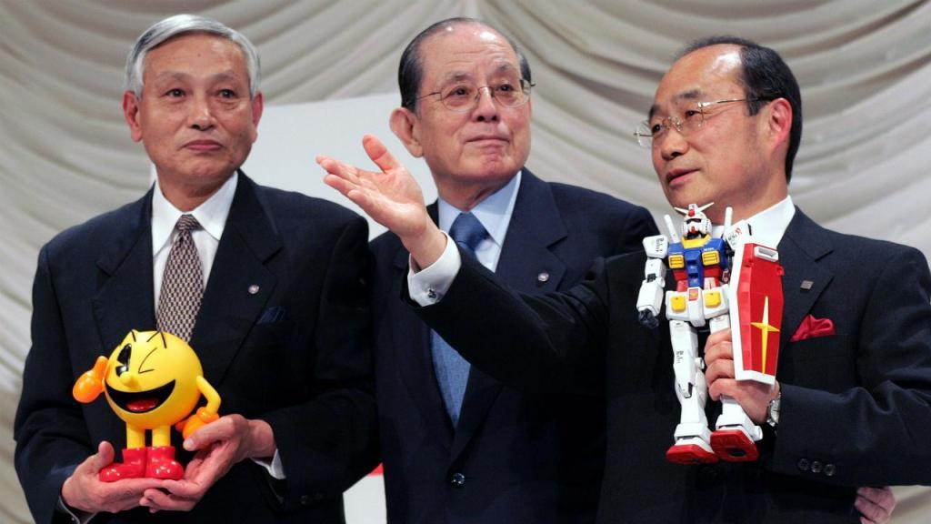 Masaya Nakamura, ao centro, ladeado pelo presidente da Bandai Takeo Takasu (direita) e Kyushiro Takagi (esquerda)