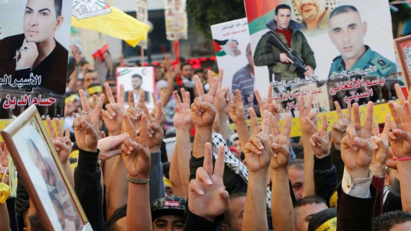 Palestinianos erguem fotografias de parentes presos