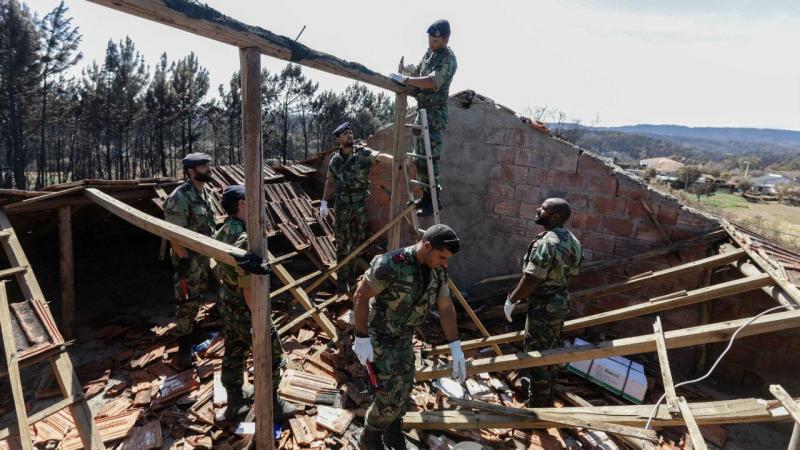 Fuzileiros da Marinha portuguesa colocam um toldo para substituir o telhado de uma habitação destruída, durante o incêndio, em Pedrógão Grande