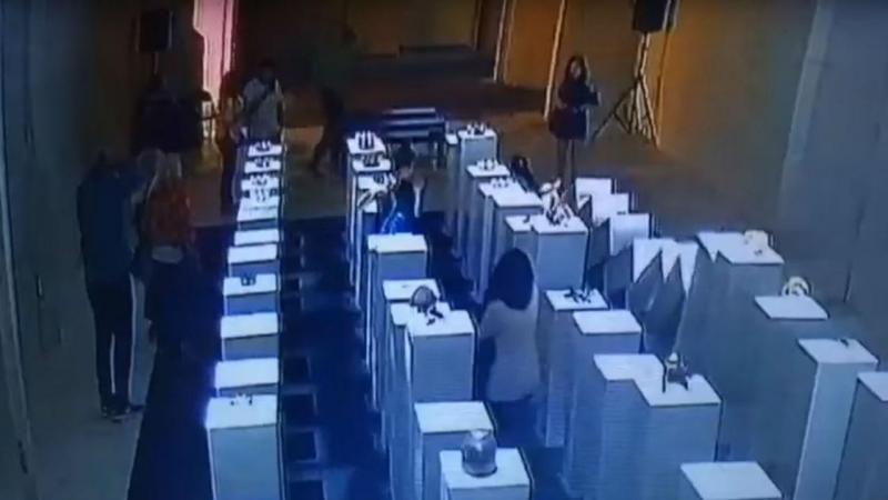 Mulher derruba colunas com esculturas a tirar uma selfie