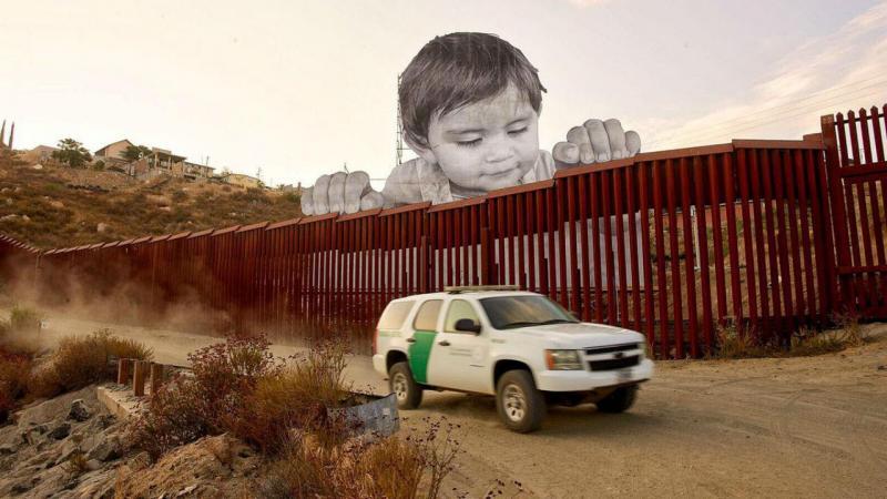 Criança a olhar para a fronteira entre o México e Estados Unidos