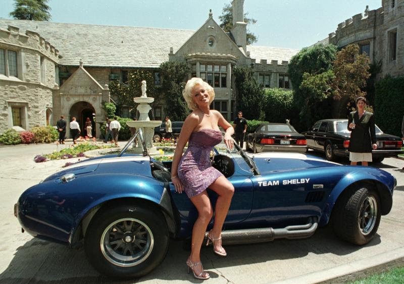 Coelhinha da Playboy em frente à Mansão com um carro