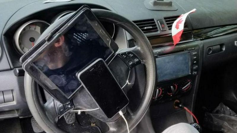 Homem com telemóvel e tablet ao volante