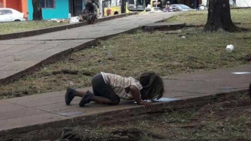 Menina bebe água do chão
