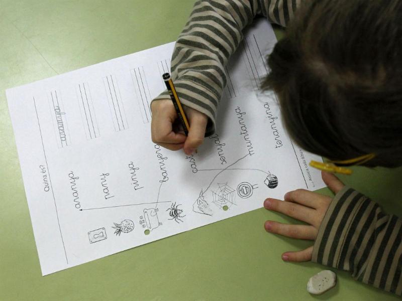 Criança da primária faz exercício escrito