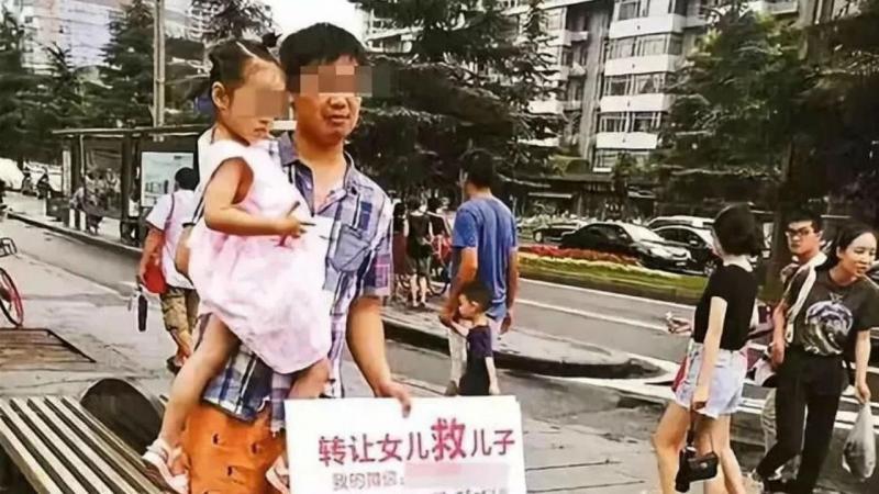 Pai fotografado na rua com a filha nos braços e um cartaz, no qual propõe oferecer a criança a quem pague o tratamento do filho