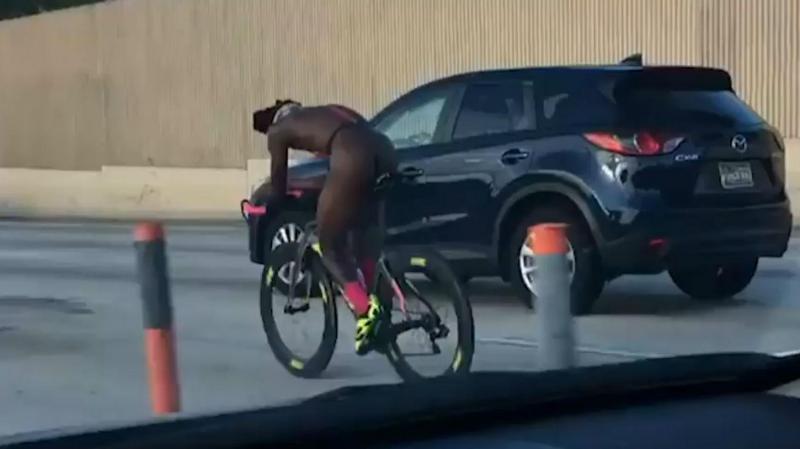 Ciclista nu na autoestrada (reprodução vídeo do «Miami Herald»)