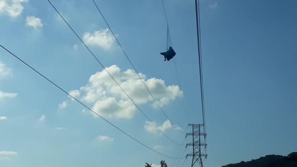 O homem preso nos fios de dois postes de eletricidade
