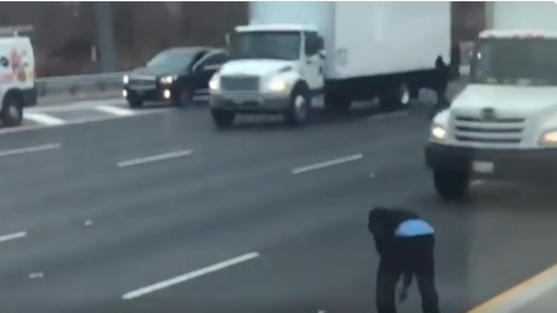 O funcionário da empresa que transportava o dinheiro a tentar reavê-lo numa autoestrada de Nova Jérsia