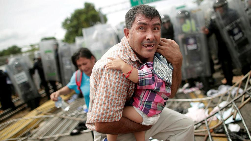 Outubro 2018: migrante das Honduras protege a filha bebé de confrontos na fronteira do México