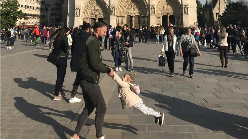 Homem e criança a brincarem em frente à Catedral de Notre-Dame