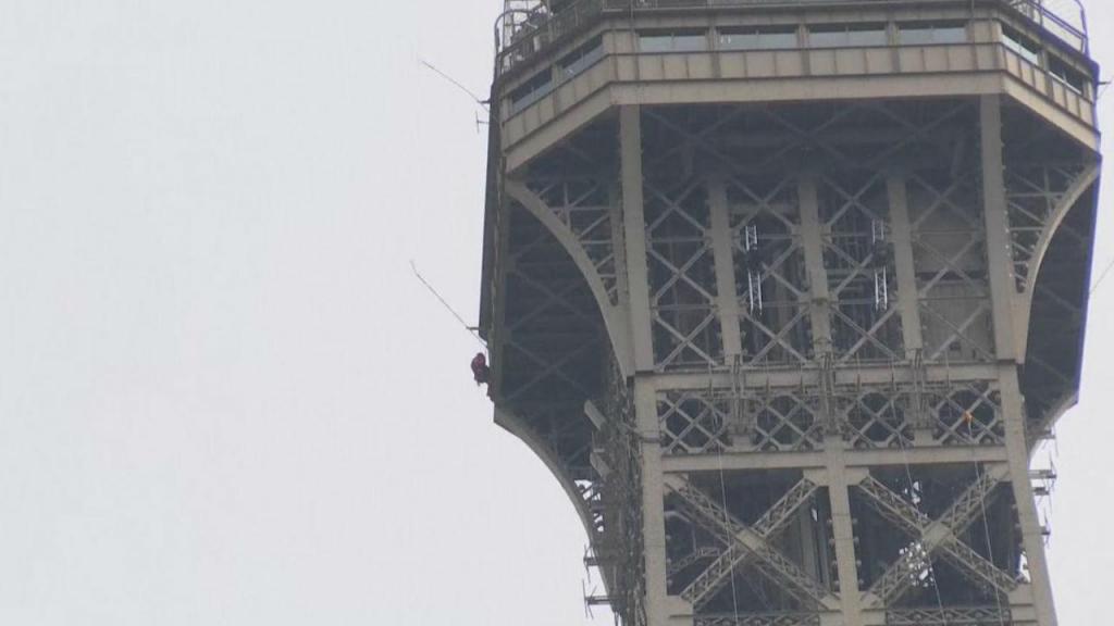 Homem escala Torre Eiffel
