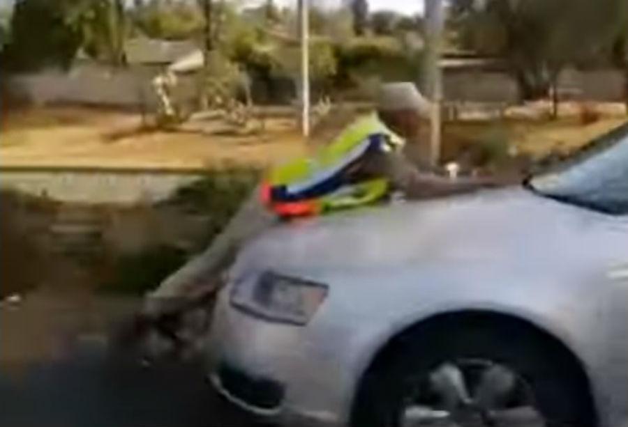 Polícia em cima do capô de um carro (reprodução YouTube)