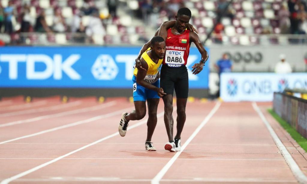 Guineense Dabó carrega arubano Busby até à meta nos Mundiais de Atletismo de Doha (EPA/SRDJAN SUKI)