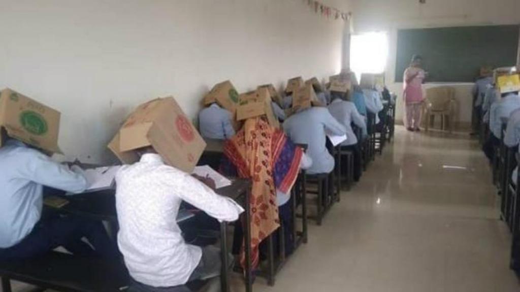 Estudantes com caixa na cabeça para não copiarem