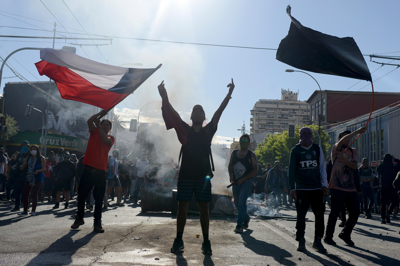 Rapaz ergue a bandeira do Chile nos protestos/API