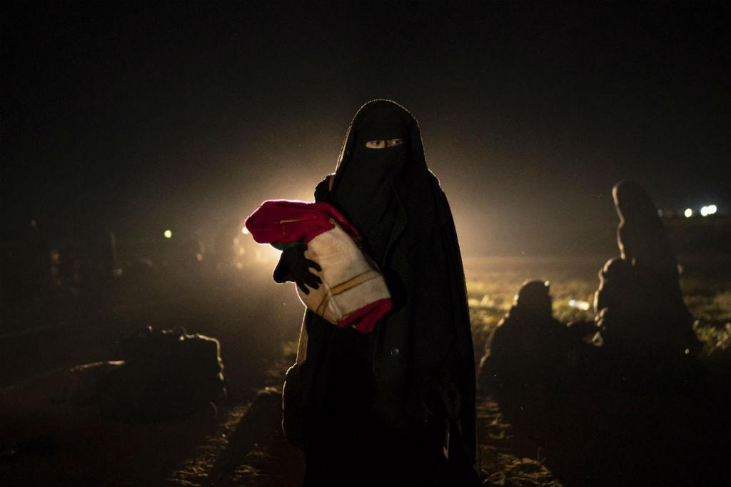 Uma mãe e o seu bebé, que foram retirados do último reduto controlado pelo Estado Islâmico na Síria, em Baghouz, caminham no deserto depois de revistados pelas forças democráticas sírias, apoiadas pelos EUA