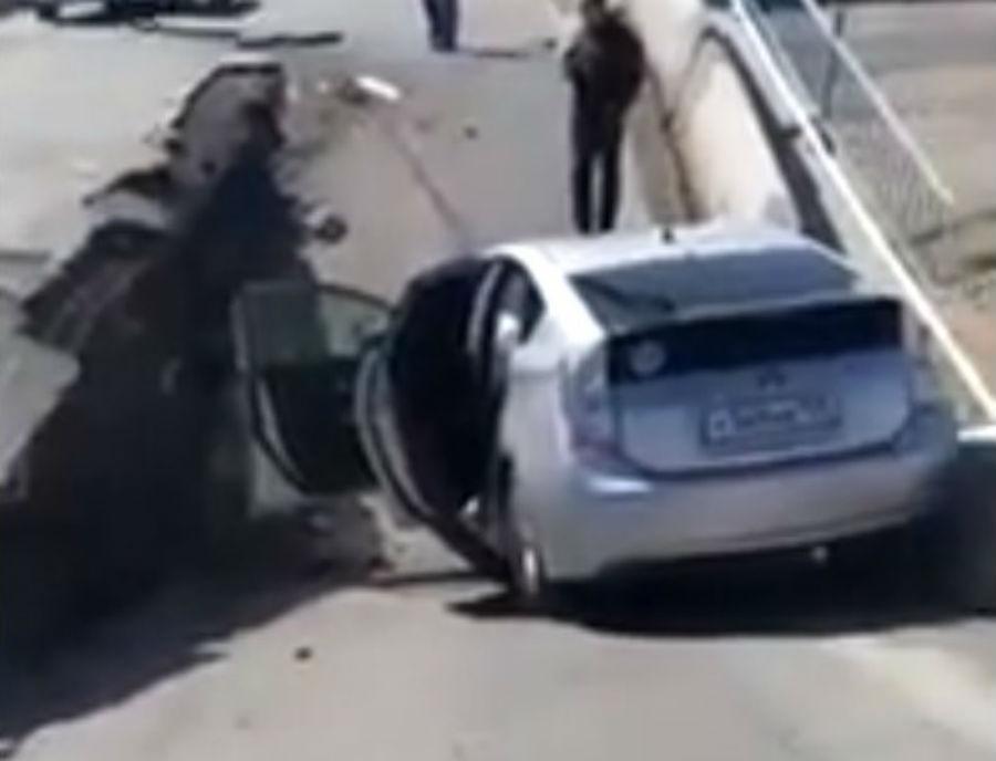 Carro cai em buraco que se abre na estrada (reprodução YouTube)