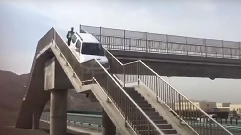 Condutor atravessa ponte pedonal (reprodução YouTube «South China Morning Post»)