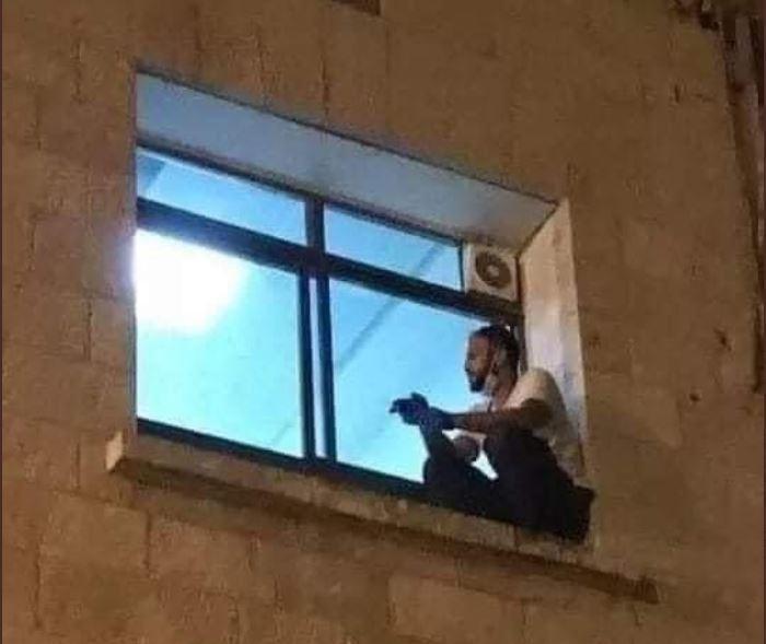 Jovem sentado na janela do hospital onde a mãe estava internada com Covid-19