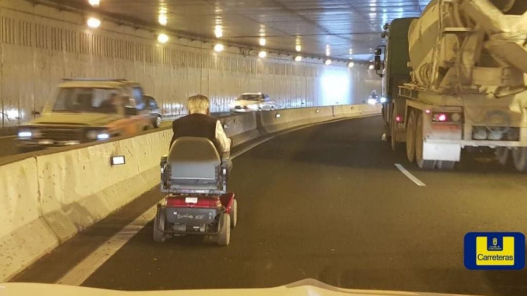 Idoso atravessa túnel em cadeira de rodas