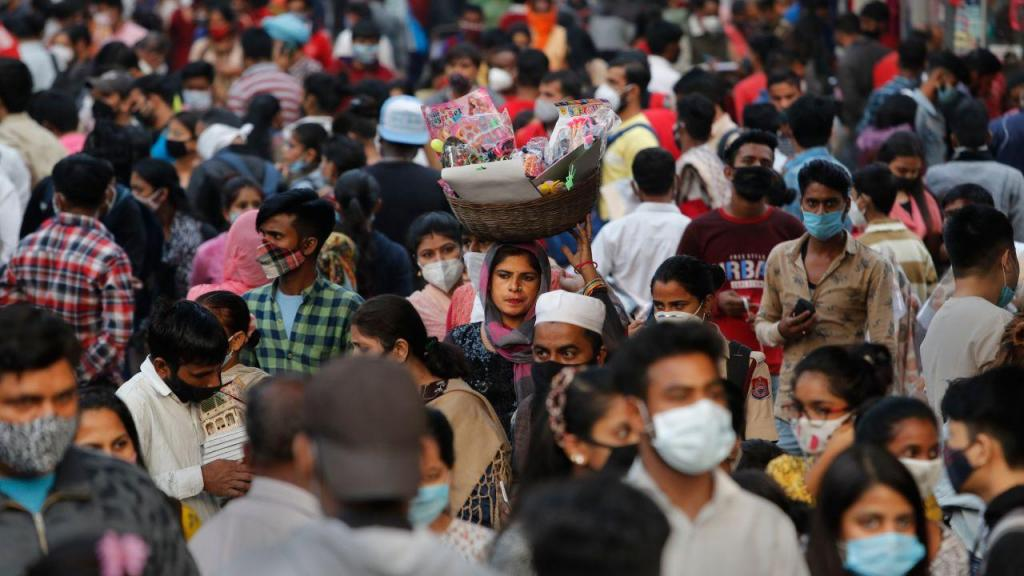 Covid-19: mulher caminha sem máscara num mercado apinhado na Índia