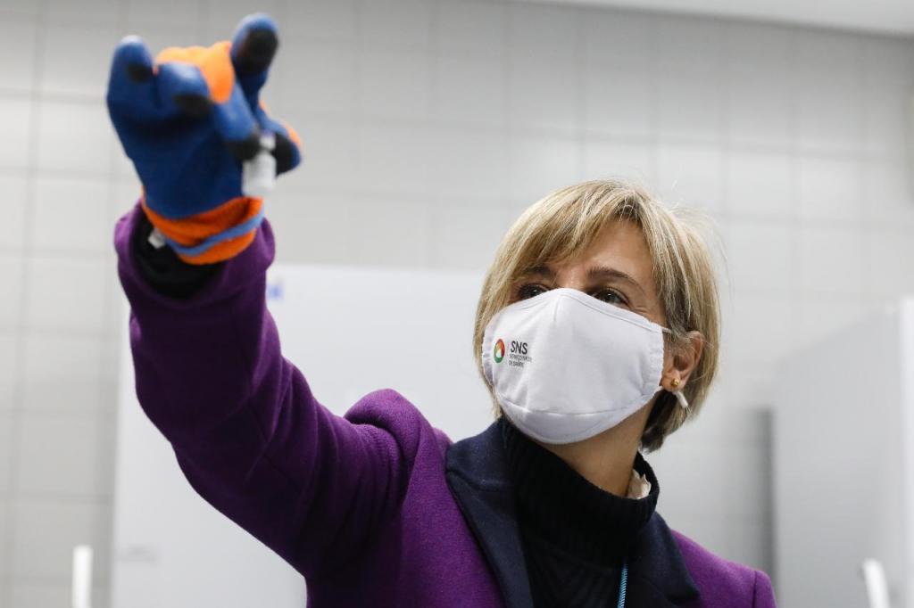 Marta Temido segura um frasco do primeiro lote das vacinas contra a Covid-19