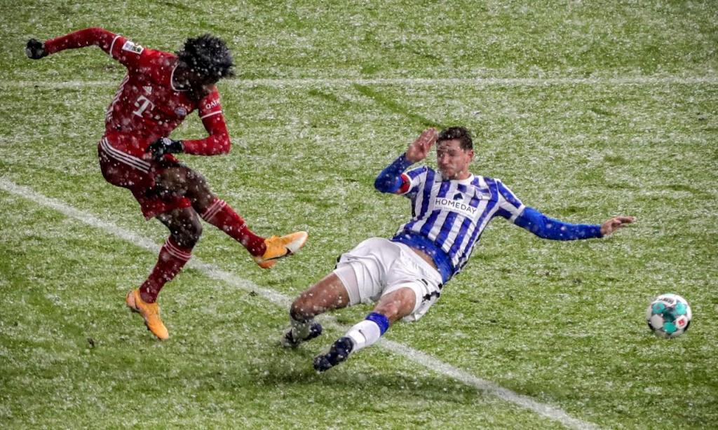 Kingsley Coman remata perante Niklas Stark para o primeiro golo no Hertha Berlim-Bayern Munique (Michael Sohn/EPA)