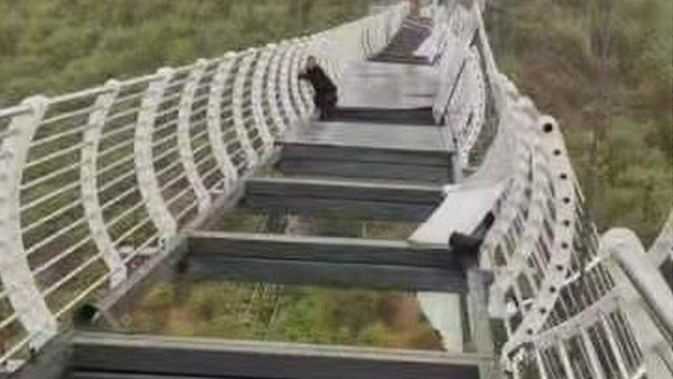 Homem pendurado em ponte de vidro