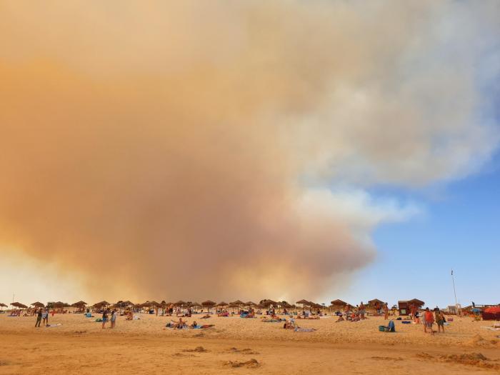 Praia algarvia com fumo dos incêndios